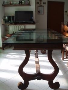 vista frontale tavolo antico con piano in cristallo